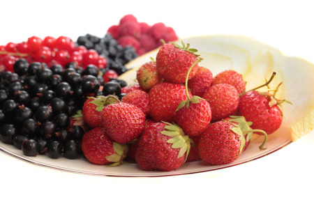 black currants: A plate of fruits: strawberries on the forefround and melon, black currants, red currants, bilberries, raspberries on the background