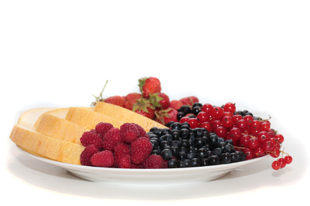 bilberries: A plate of fruits: melon, strawberries, black currants, red currants, bilberries and raspberries. Stock Photo
