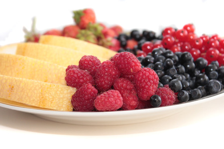black currants: A plate of fruits: raspberries on the forefround and melon, strawberries, black currants, red currants, bilberries on the background Stock Photo