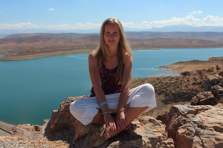 powerfull: A young woman sit on the rock and look at the camera.