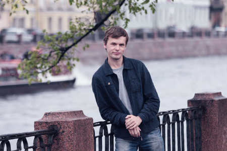 Young man walking on the Fontanka river embankment. Historical centre of St. Petersburg.