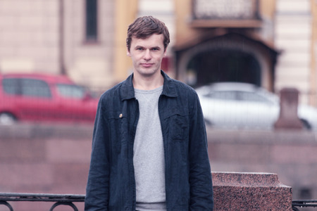 Portrait of young man in european city.