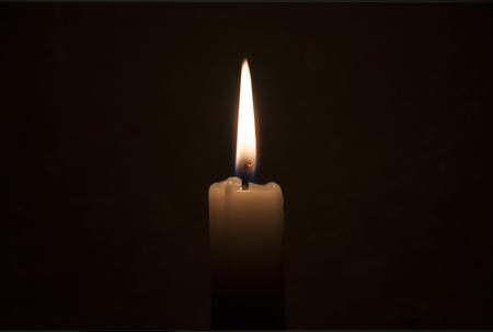 Fiamma di candela da vicino su uno sfondo scuro