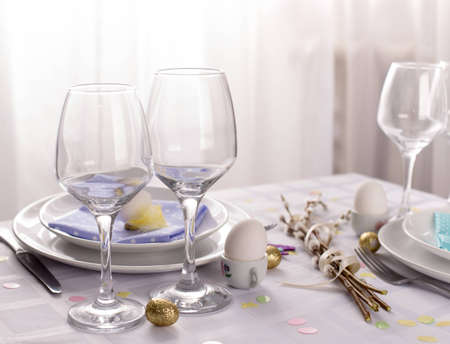 easter table setting with eggs willow branches on white background