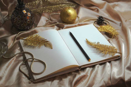 Christmas time, xmas decoration, happy new year 2020, gold notebook, bucket list, to do list and plans, candle on the table with the silk and feathers, warm winter cozy interior, letter to Santa