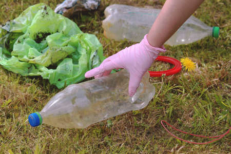 Saving the planet earth from pollution of plastic. Dandelion sprout and bottle on the green grass. Save earth from decaying plastic decomposition