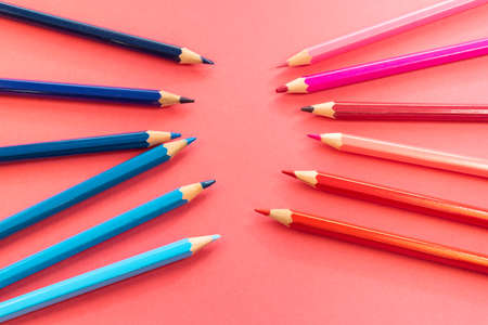 Blue and pink pencils in front placed disorganized facing each other and tilted up on a pink background