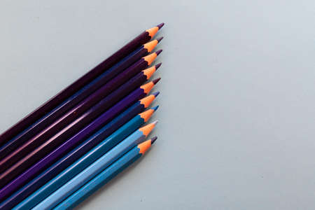Blue pencils placed in parallel and inclined upwards on a blue background