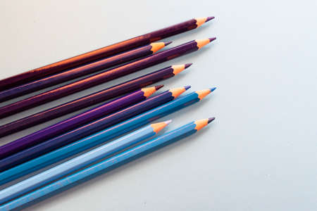 Blue pencils arranged disorganized and tilted up on blue background