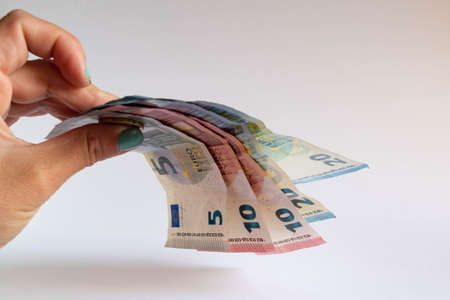 Hand holding some euro bills on white background