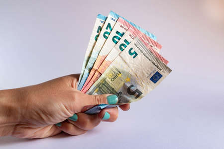 Hand holding several euro bills on white background Stok Fotoğraf