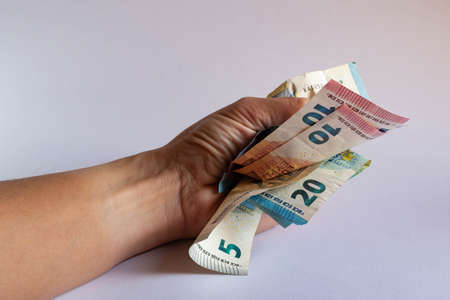 Clenched fist squeezing and crumpling some euro bills on white background Фото со стока