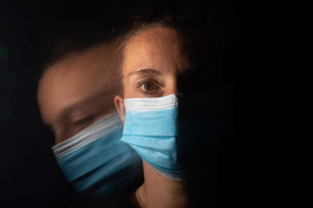 Dark portrait of a serious woman with only half her face lit up on a black background looking sad or in a depression. The woman is wearing a surgical mask. The face unfolds into another blurred and equally sad face. Depression during the coronavirus.