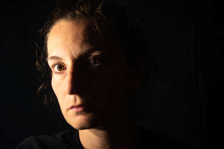 Dark portrait of a serious woman with her face partially lit. The woman is staring blankly showing sadness or anxiety Archivio Fotografico