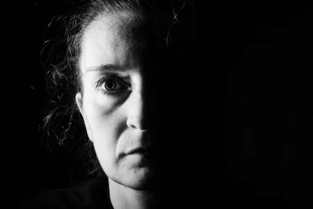 Dark portrait of a serious woman with only half her face lit up on a black background looking sad or in a depression. Portrait in black and white