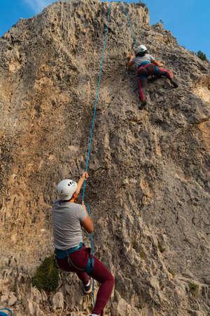 Boy firmly belaying a girl who is climbing on a stone wall outdoors