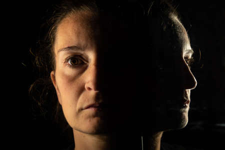 Dark portrait of a serious woman with only half her face illuminated on a black background that is unfolded in the reflection of a mirror in which her face is partially seen.