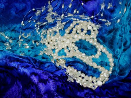 White beads and a pearl necklace on a blue silk scarf