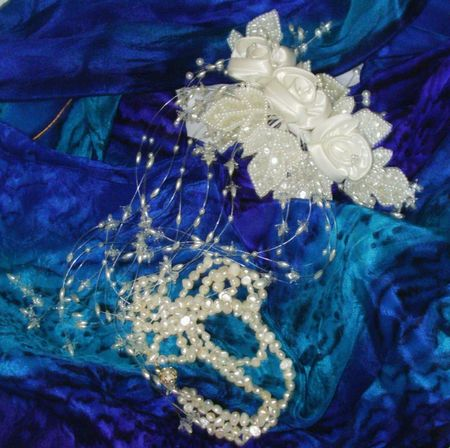 White bridal comb and pearl necklace on a silk blue scarf