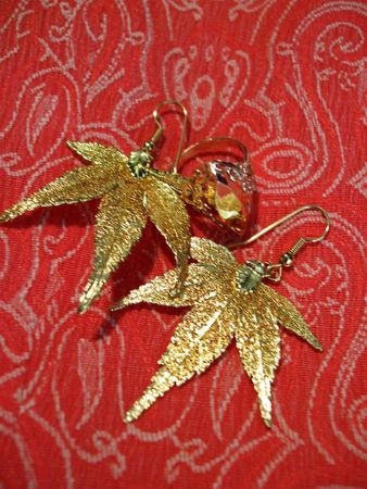 Filigree gold ring and maple earrings on coral tapestry Фото со стока