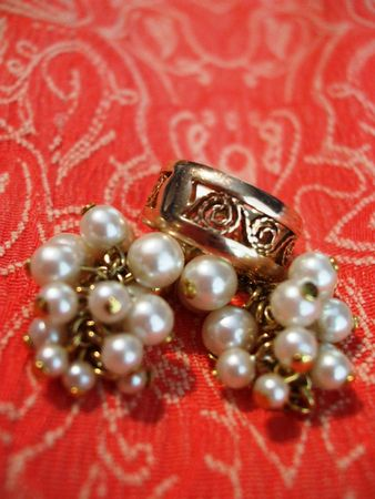 Filigree gold ring and pearl earrings on coral tapestry
