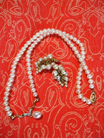 Pearl earrings and necklace on coral tapestry background