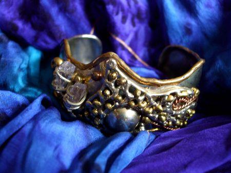 cuff bracelet: Ornate silver bracelet on a blue scarf Stock Photo