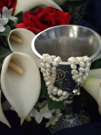 Celtic glass, pearl necklace and flowers photo