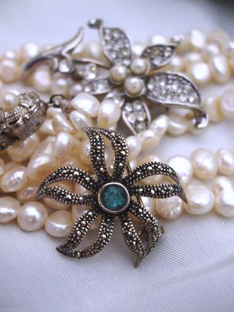 Pearl necklace with a silver flower and a blue topaz pin