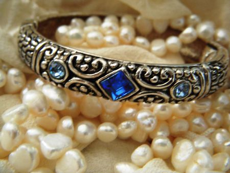 choker: Filigree silver bracelet with blue crystals and a pearl necklace