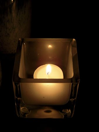 votive candle: Closeup of a votive candle in a square holder Stock Photo