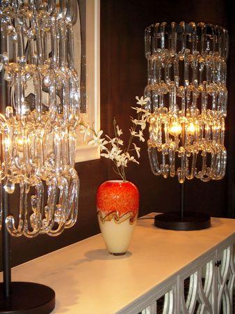 Decorative vase between two modern glass lamps Фото со стока