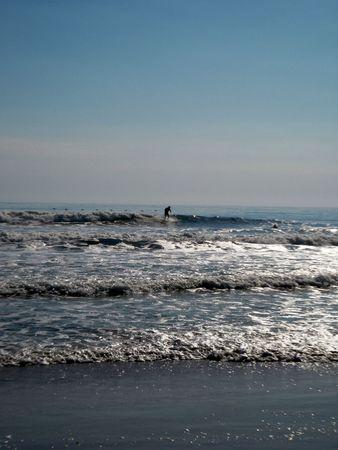 brisk: October 10, 2010 - St. Augustine beach - surfer enjoying the brisk wind Editorial