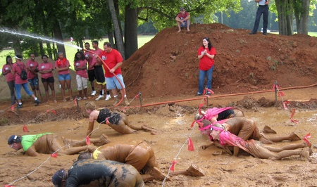 mud pit: Huntersville, NC - August 27, 2011 - Participants conquering the last obstacle - the mud pit - at the Warrior Dash Editorial