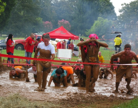 mud pit: Huntersville, NC - August 27, 2011 - Participants braving the last obstacle - the mud pit - at the Warrior Dash