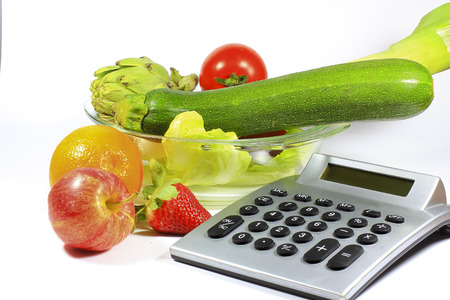 A calculator to count calories of healthy foods like fruits and vegetables with few calories Stock Photo