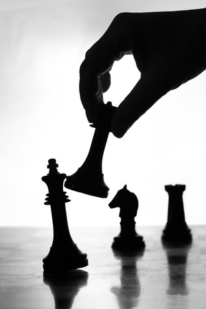 Close up view of the hand of a man going for checkmate in a game of chess using his king to knock over the opposing piece Stock Photo