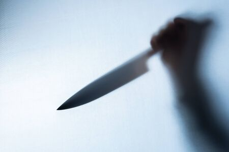 Blurred shadow of a hand holding a big and sharp knife