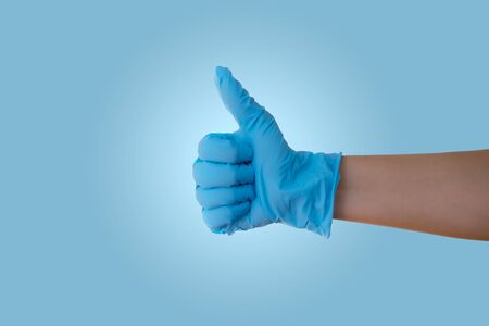Hand with blue latex medical glove with thumb up showing OK sign
