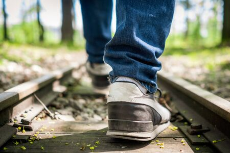 Man in sneakers walking along an empty train railway in the middle of the forest
