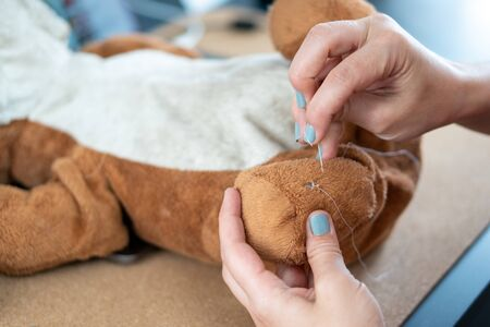 Female hand with blue nail polish sewing a ripped and dirty teddy bear
