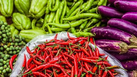 Close up of fresh and red chilli and other exotics vegetables for sale on an asian street market