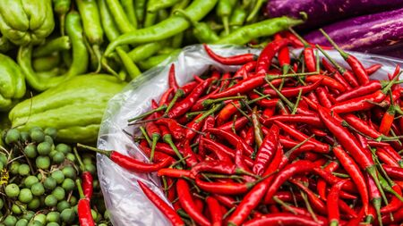 Close up of fresh and red chilli and exotics vegetables for sale on an asian street market