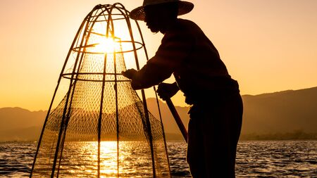 Fishermen working with a net during a golden summer afternoon in Inle Lake, Myanmar