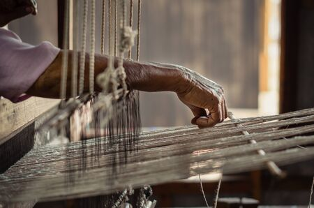 Old woman working with her hands on a rustical loom