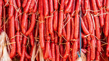 Red sausages hanging under the sun to make them dry Imagens