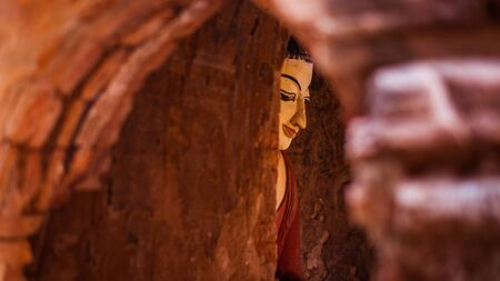 View of a Buddhist statue in red tones through an arch door in Bagan, Myanmar