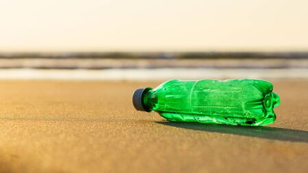 A green plastic bottle laying on the beach sand Imagens