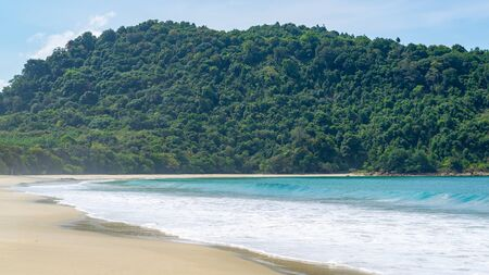 Turquoise sea water surrender by a mountain with many green trees. Empty Sin Htauk Beach in Myanmar.