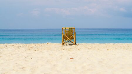 A bamboo chair in the middle of an empty beach